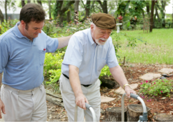 a man assisting an old man to walk